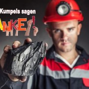 Coal miner showing lump of coal against a dark background