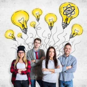Attractive young team on concrete background with drawn light bulbs. Creative idea concept